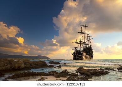 Barco pirata en mar abierto al atardecer.