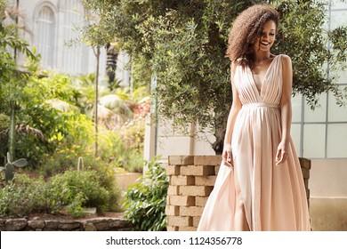 マキシドレス屋外でポーズをとるエレガントな美しいアフリカ系アメリカ人女性。