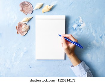 woman writes in notebook on stone blue table, Mock up with frame of seashell, top view, planning holiday by sea