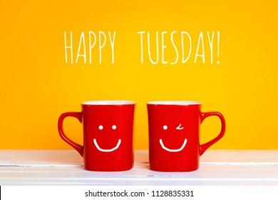 Zwei rote Kaffeetassen mit einem lächelnden Gesichtern auf einem gelben Hintergrund mit der Phrase Glücklicher Dienstag. Glückliche Kaffeetassen.