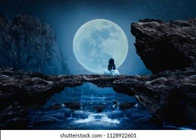 A little girl sits on a stone bridge on a beautiful full moon night.