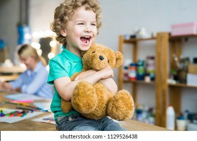 Warm getöntes Porträt des glücklichen lockigen Kindes, das fröhlich lacht und Teddybärspielzeug umarmt, kopieren Raum