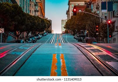夜明け、サンフランシスコ、カリフォルニア、米国の有名なカリフォルニアストリートで急な丘を上るケーブルカートラックと空の道路のローアングルトワイライトビュー