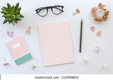 Flache Lage, Draufsicht Bürotisch Schreibtisch Arbeitsbereich mit Bürozubehör einschließlich leerem Papier für Schriftzug, Notizblock, Brille und Pflanze auf weißem Hintergrund. Attrappe, Lehrmodell, Simulation