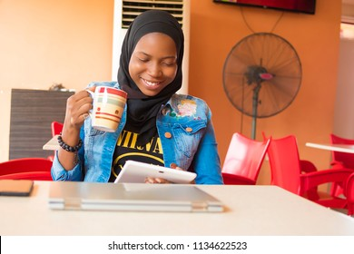 young nigerian muslim woman sitting alone in a cafe smiling while using her android tablet and holding a coffee mug