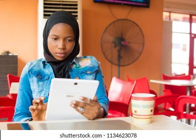 young nigerian muslim woman sitting alone in a cafe smiling while using her android tablet
