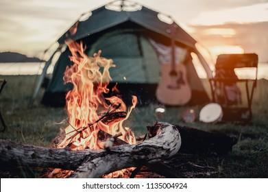 キャンプしている友人のグループ。彼らは火のキャンプの周りに座っています。