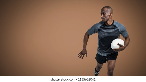 Digital composite of Rugby player running with ball with blank brown background