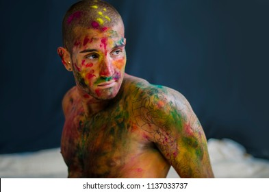 Side view of man, face painted with holi color powders.On dark background. Close-up.