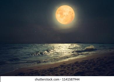 Schöner tropischer Meeresstrand der Fantasie. Vollmond (Supermond) mit Stern über Seelandschaft im Nachthimmel. Serenity Natur Hintergrund in der Nacht. Vintage und Retro Farbfilter Stil.