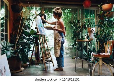 Innenaufnahme der professionellen Künstlerin, die auf Leinwand im Studio mit Pflanzen malt.