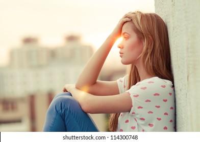 schönes einsames Mädchen, das auf dem Dach sitzt