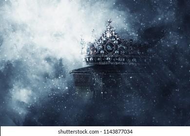 geheimnisvolles und magisches Bild der alten Krone und des Buches über dem gotischen schwarzen Hintergrund. Mittelalterliches Konzept