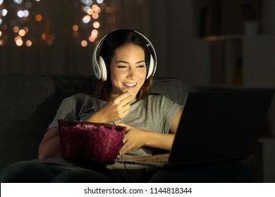 自宅のリビングルームのソファに座って夜にオンラインテレビを見ている独身女性