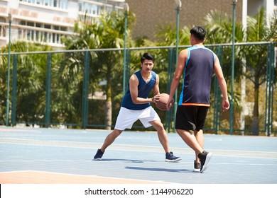 junge asiatische erwachsene Spieler, die Basketball auf dem Außenplatz spielen.