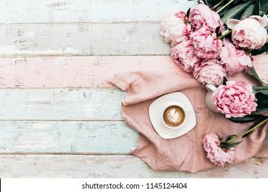 Morgenkaffeetassenkonzept. Rosa Pfingstrosenstrauß auf Weinlesehintergrund. Draufsicht, Kopierraum