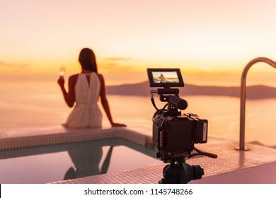 Video camera filming actress woman acting for movie on luxury hotel location behind the scenes of shoot. Professional videography equipment shooting outdoor at sunset.
