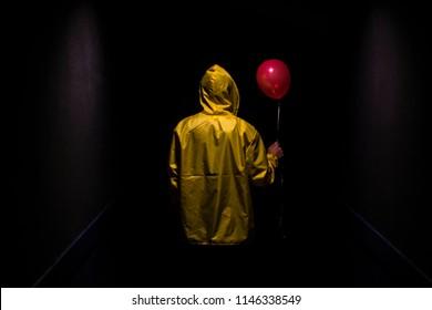 Figura amarilla encapuchada con globo rojo en oscuro corredor espeluznante
