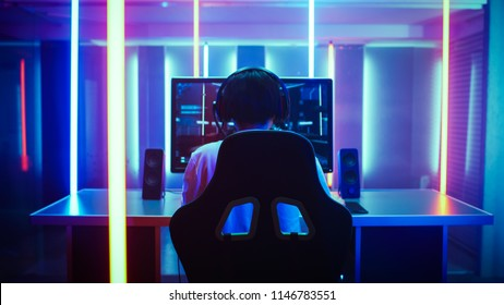 Back View Shot of the Beautiful Professional Gamer Girl Putting on Headset and Starts Playing Online Video Game on Her Personal Computer. Cute Casual Geek Girl. Room Lit by Neon Lamps in Retro Style