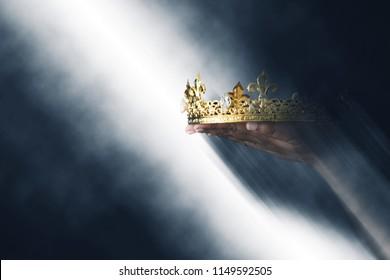 mysterieus en magisch beeld van de hand van de vrouw met een gouden kroon op een gotische zwarte achtergrond. Middeleeuwse periode concept