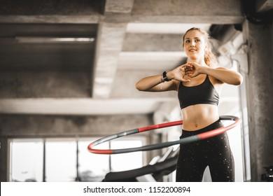 Schöne kaukasische junge Frau, die Hula Hoop in Schritt Taille Reifen vorwärts Haltung tut. Junge Frau, die Hula Hoop während einer Übungsklasse in einer Turnhalle tut. Gesunder Sportlebensstil, Fitness, gesundes Konzept.
