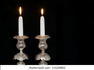 Jewish antique silver sabbath candlesticks with two lighted candles. Isolated on black; horizontal view.