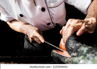 El gran salmón está en manos del experimentado chef japonés. Él está usando un cuchillo para cortar el filete de salmón para sashimi y sushi.