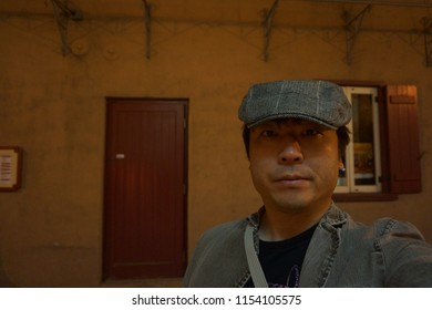 a man standing in front of red door of theatre at petit champlain in lower town of quebec old city, canada