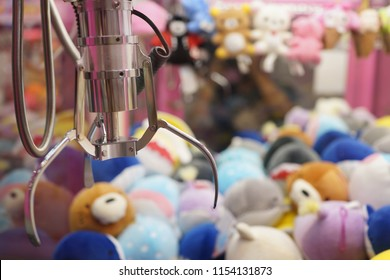 Claw capture device on background of colorful soft toys in Japanese arcade machine games centre.