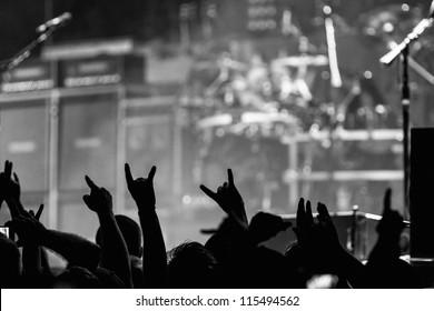 Die Menge wird verrückt und stellt bei einem Rockkonzert die Metallhörner auf