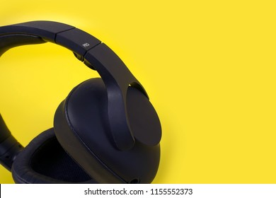 Black headphones on yellow background. Music concept with copyspace.