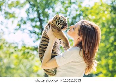 Pequeño cachorro de tigre bebé con una mujer que lo cuida y lo abraza en sus brazos en la naturaleza