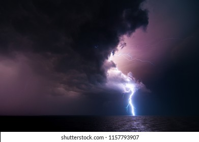Langzeitbelichtung Nachtaufnahme des Blitzes vom bewölkten Himmel zum Wasser