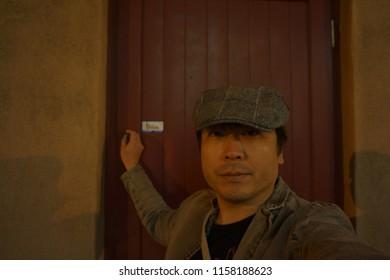 Un hombre de pie delante de la puerta roja del teatro en Petit Champlain en la parte baja de la ciudad vieja de la ciudad vieja de Quebec, Canadá