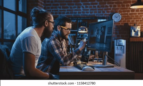 Side view of diverse group of men sitting at table with computer and coworking on creation of new cartoon movie
