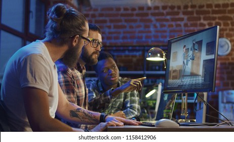 Side view of diverse group of men sitting at table with computer and coworking on creation of new cartoon