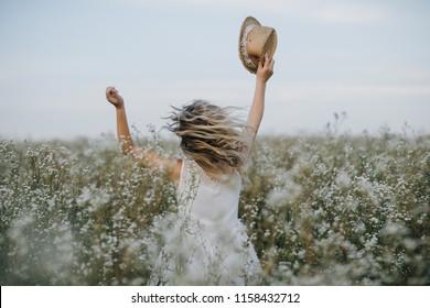 手に帽子をかぶった可愛い女の子が野の花と笑顔で野原を真摯に歩きます