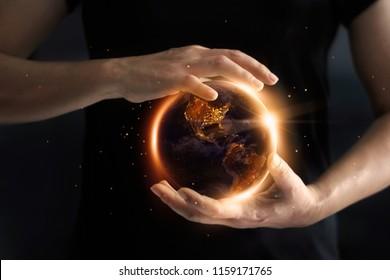 夜、環境、省エネルギーの概念で世界のエネルギー消費量を示すグローバルを持っている手。アースデー。NASAから提供されたこの画像の要素