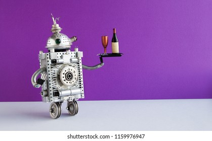 Funny robot waiter serving a tray with a bottle and wine glass. Two wheels domestic robotic character on violet wall, gray floor background. copy space, selective focus.