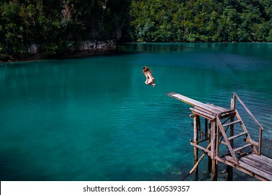 Vacation and activity. Young woman jumping on wooden springboard. Blue tropical lagoon Siargao Island, Philippines.