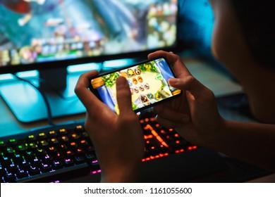 Porträt des jugendlichen Spielerjungen, der Videospiele auf Smartphone und Computer im dunklen Raum trägt, die Kopfhörer tragen und bunte Tastatur mit Hintergrundbeleuchtung verwenden