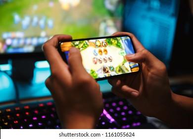Manos de un joven jugador jugando videojuegos en el teléfono inteligente y la computadora en una habitación oscura con audífonos y teclado colorido retroiluminado