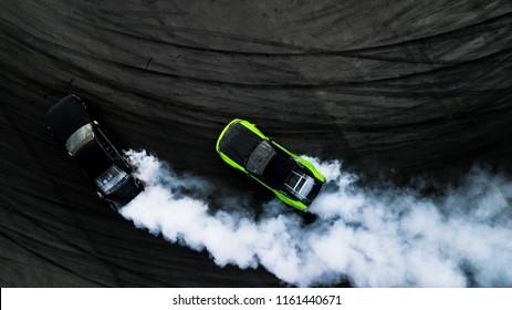 アスファルトストリートロードレーストラックでの空中トップビュー2台の車のドリフトバトル、上からの2台のレース車のドラッグビュー、車のターボのドリフト、スピードトラックで燃えているタイヤからの白い煙のレースドリフト車。