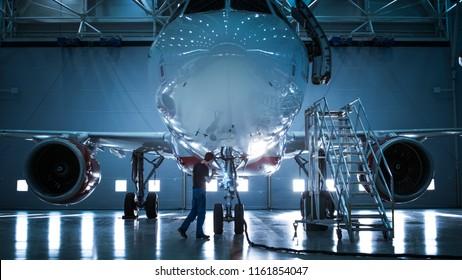 Brandneues Flugzeug, das in einem Flugzeugwartungshangar steht, während Flugzeugwartungsingenieur / -techniker / -mechaniker über Leiter / Rampe in die Kabine geht.