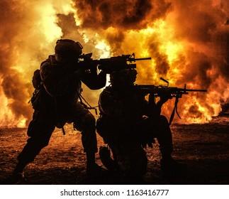 Silhouetten von zwei Armeesoldaten, US-Marinesoldaten in Aktion, umzingelten Feuer und Rauch, schossen mit Sturmgewehr und Maschinengewehr und griffen den Feind während einer Offensivmission mit unterdrückendem Gewehrfeuer an