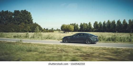 Modernes Tesla, das auf einer freien grünen Straße fährt. Elektroauto Lebensstil modernen Look. redaktionell