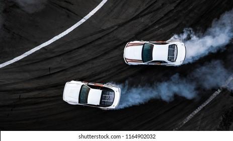Luft Draufsicht zwei Auto Drift Schlacht auf Asphalt Rennstrecke, Auto und Auto Auto Ansicht von oben, Professionelle Auto Driften, Race Drift Auto mit weißem Rauch von brennenden Reifen auf Speed Track.