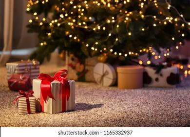 部屋のモミの木の近くの床に美しいクリスマスギフトボックス