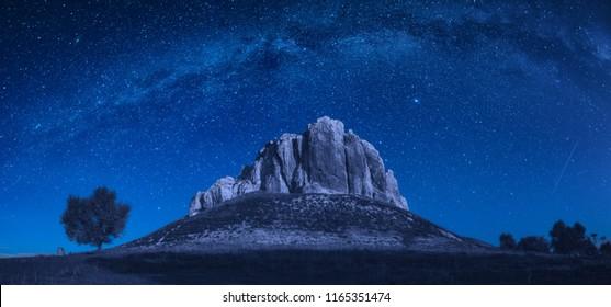 Hoher felsiger Berggipfel in einem Tal gegen Milchstraße in einem nächtlichen Sternenhimmel.