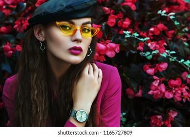 Nahaufnahme-Modeporträt der jungen schönen Frau im Freien, die trendige gelbe Sonnenbrille, Leder-Baskenmütze, Armbanduhr, Fuchsia-Farbblazer trägt und nahe blühenden rosa Blumen aufwirft. Kopieren, leerer Raum